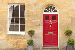 Puertas principales rojas elegantes en una casa de piedra de oro foto de archivo libre de regalías