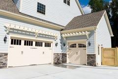 Puertas residenciales del garaje del coche de la casa tres Fotografía de archivo libre de regalías