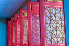Puertas rojas de madera hermosas y ventanas del estilo chino con el dragón Foto de archivo libre de regalías
