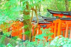 Puertas rojas del torii en Fushimi Inari Taisha Deseos escritos en japonés en los posts Foto de archivo libre de regalías