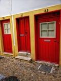 Puertas rojas en una calle estrecha imagen de archivo libre de regalías