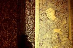 Puertas talladas antiguas cubiertas con las hojas de la laca y del oro en Wat Foto de archivo libre de regalías