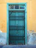 Puertas verdes viejas con la puerta de seguridad del hierro en un edificio viejo Foto de archivo