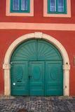 Puertas verdes y pared roja Foto de archivo