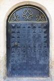 Puertas viejas arqueadas antiguas del hierro con una manija forjada y un bastidor superior imagen de archivo