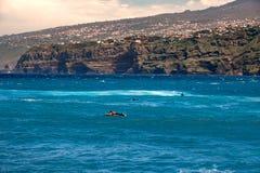 2019-03-21 Puerto de la Cruz, Santa Cruz de Tenerife Las personas que practica surf utilizan las ondas fuertes en la bahía Martia imagen de archivo libre de regalías