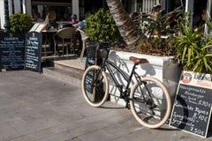 Puerto de Mogan, Gran Canaria en España - 16 de diciembre de 2017: La bicicleta negra parqueó fuera del restaurante la taberna ir fotos de archivo