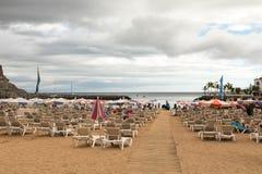 Puerto de Mogan, Gran Canaria en España - 16 de diciembre de 2017: Sunbeds y parasoles en la playa, con un paseo del tablero en Fotos de archivo libres de regalías