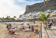 """Puerto de Mogan, Spanien †""""Januari 17, 2016: Folk på stranden som tycker om semesterorten Puerto de Mogan Gran Canaria, kanarie Royaltyfri Foto"""