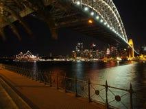 Puerto de Sydney debajo del puente con el teatro de la ópera por noche del norte Imagen de archivo libre de regalías