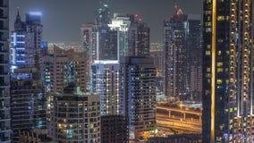 Puerto deportivo de Dubai y JLT en el timelapse de la noche, las luces que brillan y los rascacielos más altos metrajes