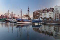 Puerto deportivo de la salida del sol con los yates amarrados y los barcos que flotan en el agua tranquila Foto de archivo