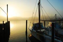 Puerto deportivo en la salida del sol en la niebla Imagenes de archivo