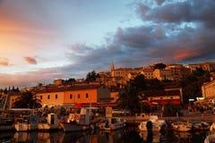Puerto deportivo y pequeña ciudad en puesta del sol Imagen de archivo