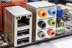 Puerto Ethernet y puertos para la conexión de dispositivos audios en la placa madre Imagen de archivo libre de regalías