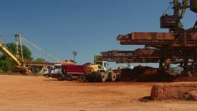 Puerto industrial del cargo con el mineral en los camiones volquete, lapso del cargamento del cargador de la rueda de tiempo almacen de video