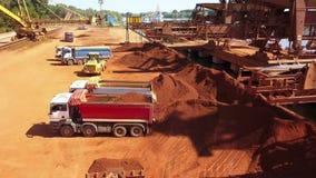 Puerto industrial del cargo con el mineral en los camiones volquete, visión aérea del cargamento del cargador de la rueda almacen de metraje de vídeo