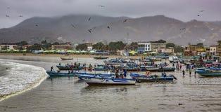 Puerto Lopez, эквадор - 12-ое сентября 2018 - рыболовы заканчивает их сети отладки дня, очищая шлюпки, и разговаривать с стоковые изображения