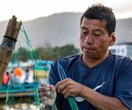 Fisherman repairs his net Royalty Free Stock Image