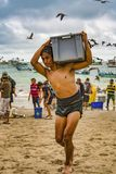Puerto Lopez, Ecuador - September 12, 2018 - man carried bin of fresh fish from boat to waiting ice truck wholesale. Puerto Lopez, Ecuador - September 12, 2018 royalty free stock image