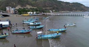 Puerto Lopez, Ecuador - 20180913 - surrantenn - flyg längs kusten som fylls med fartyg och folk in mot pir arkivfilmer