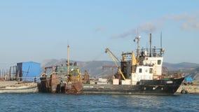 Puerto marítimo Naves viejas que permanecen en bahía Barco viejo de los pescados en muelle Metal del moho Reflexión del cielo nub almacen de video