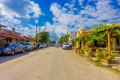 Puerto Morelos, México - 10 de enero de 2018: La vista al aire libre de algunas casas con muchos coches parqueó en la calle de Pu Fotografía de archivo