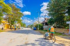 Puerto Morelos, México - 10 de janeiro de 2018: Homem não identificado que conduz seu triciclo nas ruas de Puerto Morelos Imagem de Stock