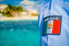 Puerto Morelos, Mexico - Januari 10, 2018: Slutet av den selektiva fokusen av den mexikanska skölden skrivev upp ut i enskjorta i Royaltyfri Fotografi