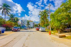 Puerto Morelos, Mexico - January 10, 2018: Outdoor view of some houses with many cars parked in the street of Puerto Stock Photos