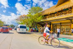 Puerto Morelos, Mexico - January 10, 2018: Unidentified woman driving her bike in the streets of Puerto Morelos, Yucatan royalty free stock photo
