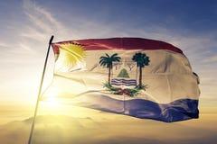 Puerto Plata Province of Dominican Republic flag textile cloth fabric waving on the top sunrise mist fog. Beautiful stock photo