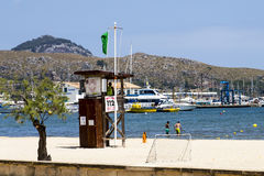 PUERTO POLLENSA, MALLORCA - 27 JULY 2015 Lifeguard in station wa. Tching over holiday makers in the sea in Puerto Pollensa, Mallorca. Grren flag flying stock photography
