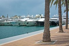 Luxury yachts in Puerto Portals marina. PUERTO PORTALS, MALLORCA, SPAIN - APRIL 24, 2018: Luxury yachts moored in the marina of Puerto Portals on an overcast day Stock Photography