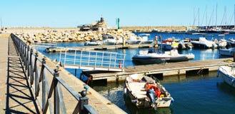 Puerto, puente, roca, ondas y barcos de Rio Marina en Toscana, en la isla de Elba, Italia Imágenes de archivo libres de regalías
