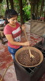 Young latin woman toasting cacao beans in a small gas kitchen. Toasting cocoa beans is a part of the process for making handmade c Stock Images