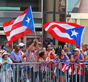 Puerto Rican Day Parade. Spectators at the National Puerto Rican Day Parade, holding large flags in New York City along 5th avenue Stock Photography