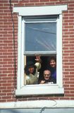 A Puerto Rican family waving from their apartment window, Wilmington, DE Stock Photo