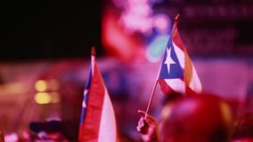 Puerto Rican Flags being held at Festival during evening. Evening shot of two Puerto Rican flags being held outdoors at an event.  SInce it is a close-up, aside stock video