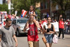 The Puerto Rican People`s Parade. Chicago, Illinois, USA - June 16, 2018: The Puerto Rican People`s Parade, Puerto rican man with a child waving the puerto rican stock image