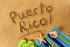 Puerto Rico beach sand word writing. The words Puerto Rico written on a sandy beach, with beach towel, starfish and flip flops Stock Image