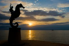Puerto Vallarta Sunset. Colorful Sunset in Puerto Vallarta with silhouette of statue and pirate ship in far background stock photography