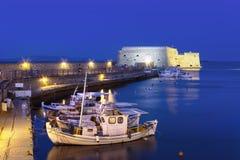 Puerto viejo de Heraklion con la fortaleza de Koules, los barcos y el puerto deportivo venecianos en la noche, Creta foto de archivo libre de regalías