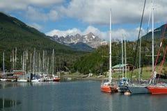 Puerto Williams, strzępiaste góry nad kolorowymi żaglówkami obraz royalty free