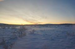 Puesta del sol ártica fría para las vacaciones de la luna de miel o el invierno de la diversión que viaja para el papel pintado fotografía de archivo libre de regalías