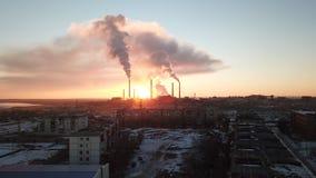 Puesta del sol épica en el fondo de una fábrica que fuma El sol rojo con los rayos brillantes va más allá de las fábricas y de la imagenes de archivo