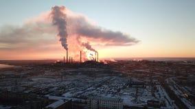 Puesta del sol épica en el fondo de una fábrica que fuma El sol rojo con los rayos brillantes va más allá de las fábricas y de la foto de archivo
