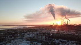 Puesta del sol épica en el fondo de una fábrica que fuma El sol rojo con los rayos brillantes va más allá de las fábricas y de la fotografía de archivo libre de regalías