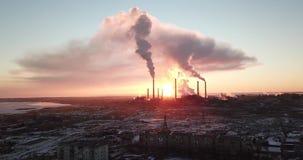 Puesta del sol épica en el fondo de una fábrica que fuma El sol rojo con los rayos brillantes va más allá de las fábricas y de la metrajes