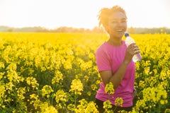 Puesta del sol afroamericana del agua potable del adolescente de la muchacha de la raza mixta Fotografía de archivo libre de regalías